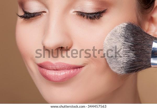 Nahaufnahme des Gesichts einer jungen Frau, die mit einer Bürste Pulver auf die Wange bekommt. Sie lächelt. Ihre Augen sind geschlossen