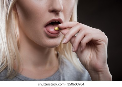 Close up of face of young woman taking drug. The drug addict is standing and putting a pill into her mouth