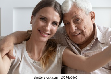 Close up faces of elderly 80s grandfather adult 30s granddaughter hands holding camera smiling make self portrait webcam view, older younger generations relatives people taking photo or record video