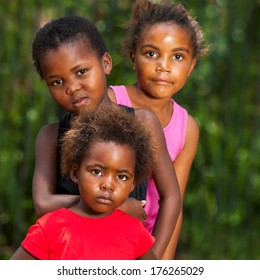 Close up facial portrait of three african girls together outdoors.