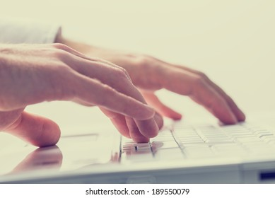 Close up faded effect retro style image of the hands of a man typing on a laptop keyboard.