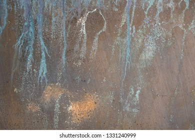 close up of faded paint streak abstract design on textured metal surface