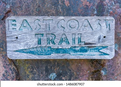 Close up of a faded wooden East Coast Trail sign with arrow, displayed on a rock background, near Fort Amherst Lighthouse, St. John's, Newfoundland.
