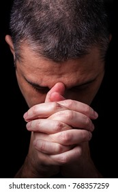 Close up of faithful mature man praying, hands folded in worship to god with head down and eyes closed in religious fervor. Black background. Concept for religion, faith, prayer and spirituality.