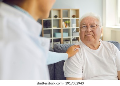 Close up of a family doctor visiting, supporting, and encouraging his or her elderly patient at home. Focused man sits on the couch and listens to treatment advice. Concept of health care and support.
