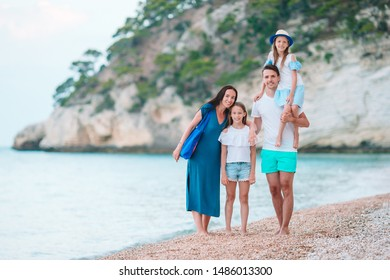 Close up family of four on the beach playing and having a good time