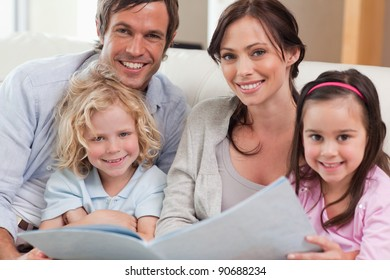 Close up of a family looking at a photo album in a living room