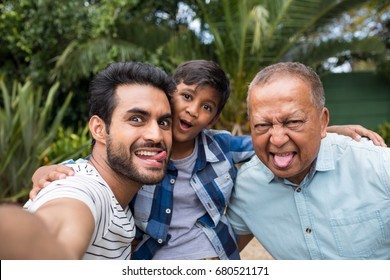 Close up of family making faces while standing against plants at park