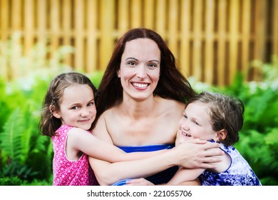 A close up family picture of two daughters on either side of their mother giving her a hug.