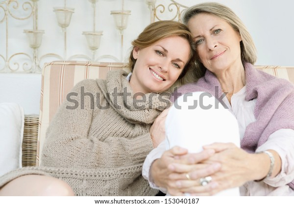 Close up family portrait of an adult daughter with her mature mother leaning on each other and being affectionate while relaxing on a sofa at home, outdoors.