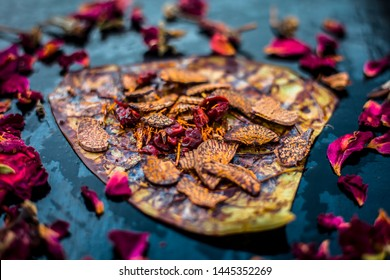 Close up of Famous Indian traditional masala pan or meetha pan on black surface with some rose water consisting of coated sauf,supari,sweeteners and some coconut powder.