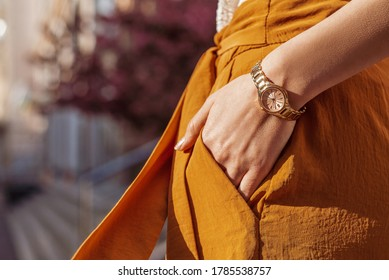 Close up of fashion accessories, street style details: elegant golden wrist, hand watch. Woman posing in European city. Copy, empty space for text