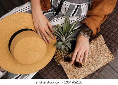 Close up fashion details of bohemian woman. Straw hat, pineapple and stylish  purse.