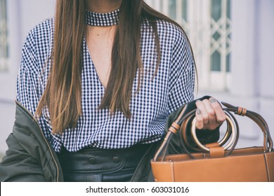 close up fashion details, woman holding her brown elegant bag. ideal spring outfit accessories.fashion blogger posing in a gingham check top and a bomber jacket.