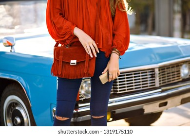 Close up fashion details of woman posing in front of vintage car, modern boho stylish trendy outfit, navy denim pants, orange blouse and bag, matching accessories, holding smartphone, spring summer.