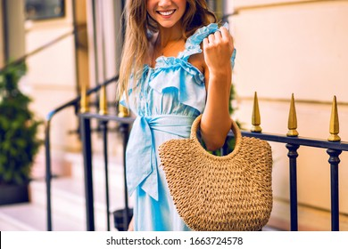 Close up fashion details of woman smiling and holding straw bag, wearing trendy dress posing near luxury shop.
