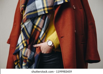 close up fashion details, young fashion blogger wearing modern wrist watch and a brown double breasted coat with a check scarf. ideal fall outfit accessories.