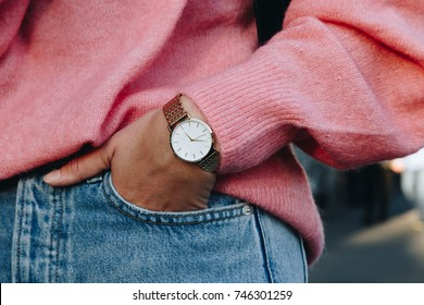 close up fashion details, young fashion blogger wearing a pink oversized fluffy sweater, a golden watch and necklace and a black handbag, ideal fall outfit accessories.