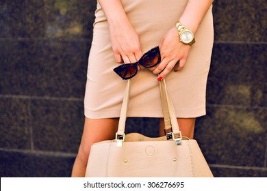 Close up fashion details, young business woman holding bag and retro sunglasses, golden jewelry, warm colors.