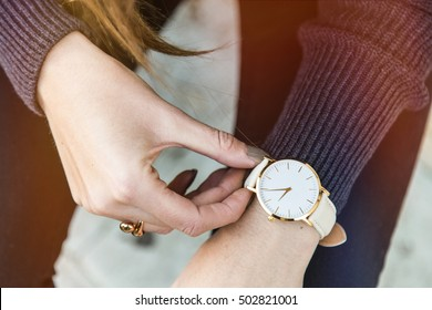 close up fashion details, young business woman holding her golden watch. graded in warm colors.