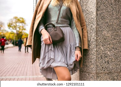 Close up fashion details of young elegant woman posing on the street, wearing silk dress, silver sweater, crossbody bag and luxury cashmere coat, soft toned colors, jewelry and accessories.