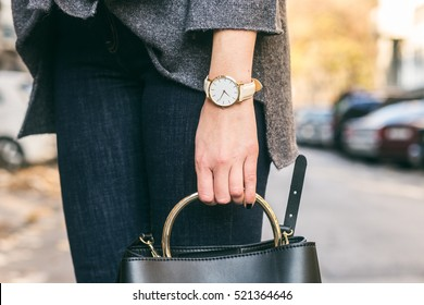close up fashion details, young fashionable woman holding her bag. wearing golden jewelry, and white watch.