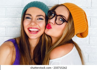 Close up fashion lifestyle portrait of two young hipster girls best friends, wearing bright make up and similar trendy hats, making funny faces and have gray time. Urban white brick wall background.
