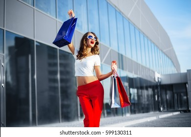 Close up fashion lifestyle portrait young hipster girl, with shopping bags walking out from shop
