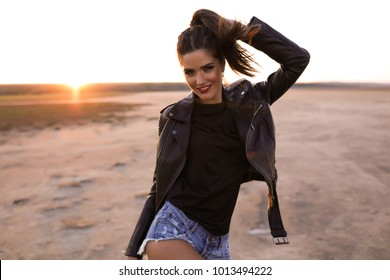 Close up fashion Outdoor lifestyle fashion portrait of young stylish beautiful woman walking on street,wearing khaki trendy outfit,biker bomber coat,black t shirt,vintage sunglasses,hands,style