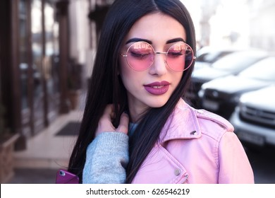 Close up fashion Outdoor lifestyle fashion portrait of young stylish beautiful  woman walking on street,wearing pink trendy outfit,biker leather coat,grey dress,vintage pink  sunglasses