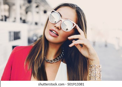 Close up fashion portrait of amazing young woman with perfect skin, full lips ,  in stylish sunglasses, bright pink jacket.