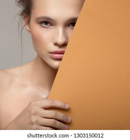 Close up fashion portrait of beautiful woman. Clear natural skin. Orange paper blank.
