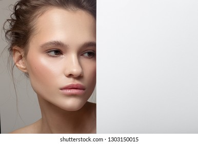 Close up fashion portrait of beautiful woman. Clear natural skin. White paper blank.