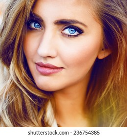 Close up fashion portrait of blonde sexy girl with magnetic blue eyes, stylish hairstyle and bright makeup.