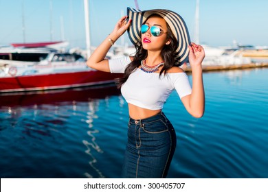 Close up fashion portrait of elegant asian girl in sunglasses  posing  in  yacht club wearing straw hat, bright make up,  hight crop top and jeans skirt , summer vacation mood.