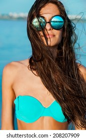Close up fashion  portrait of a girl in a stylish round glasses and with wet hair on sea background.Wearing blue swimwear.