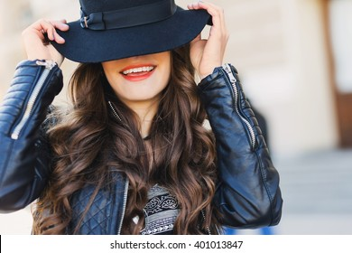 Close up fashion portrait of pretty seductive young woman with  wool hat  smiling, laughing ,  posing outdoor. Red lips, wavy hairstyle.