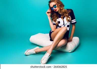 Close up fashion portrait of pretty sportive woman in stylish sunglasses, basketball t-short and white sneakers sitting on white pillow against bright aqua background .