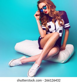 Close up fashion portrait of pretty sportive lady  in stylish sunglasses, basketball t-short and white sneakers sitting on white pillow against bright aqua background .