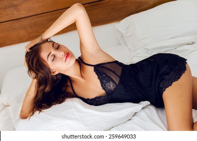 Close up fashion portrait  of sexy tanned fit woman in luxury silk lingerie, laying at big white bed. Close eyes and feel relax.