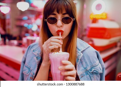 Close up   fashion  portrait of stylish brunette woman drinking tasty sweet milk shake  in retro style American cafe with neon lights.