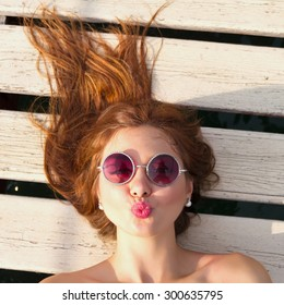 Close  up fashion portrait of teenage girl.Top view of a woman lying on her back, blowing a kiss.Indoor lifestyle or fashion portrait of stylish teenage model with curled red amazing hair,having fun.