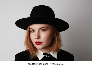 Close up fashion portrait of trendy woman in stylish clothes and black hat posing on white background