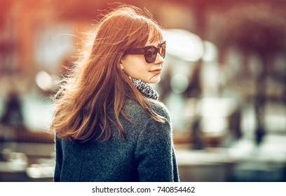 Close up fashion portrait of trendy woman in coat at the city street