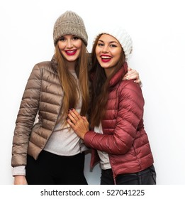 Close up fashion portrait of Two cheerful beautiful girls friends posing for camera inside. Bright makeup, hats and winter casual style. White background, not isolated.Having fun together.