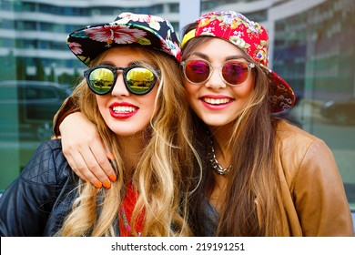 Close up fashion portrait of two pretty girls , wearing leather jackets swag hats and mirrored sunglasses, having blonde and brunette hairs and bright lips. Best friends positive portrait.