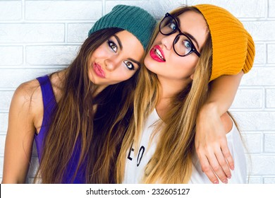 Close up fashion portrait of two young pretty hipster girls wearing bright make up hats and glasses. Studio portrait of two cheerful best friends sisters having fun and making funny faces.