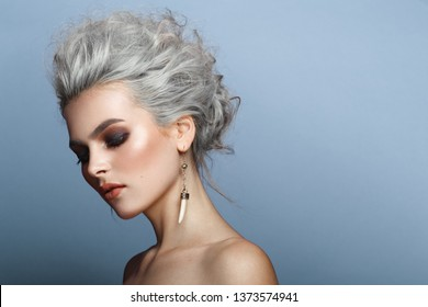 Close up of a fashion portrait of a young woman with stylish blonde grey hairstyle, with a penetrating look, smokey eyes, perfect makeup, naked shoulders, headshot, isolated on a blue background.
