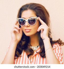 Close up fashion portrait of young woman posing at beige background in retro cat eye sunglasses. Sixties style, pastel film colors.