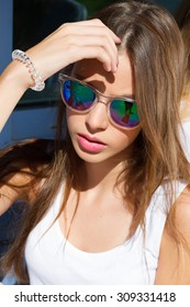 Close up fashion portrait of young woman. Close up fashion portrait of pretty hipster teenage girl with long brunette hairs, wearing stylish trendy mirrored blue sunglasses, bright colors.